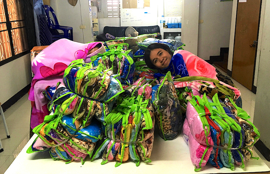 Head teacher, Ying, with a bundle of blankets before distribution