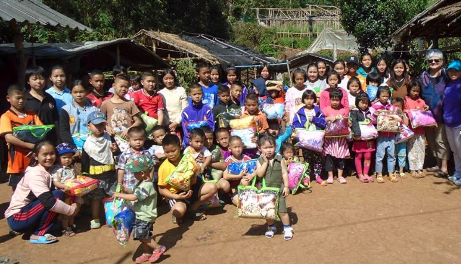 Group photo with children bearing blankets.